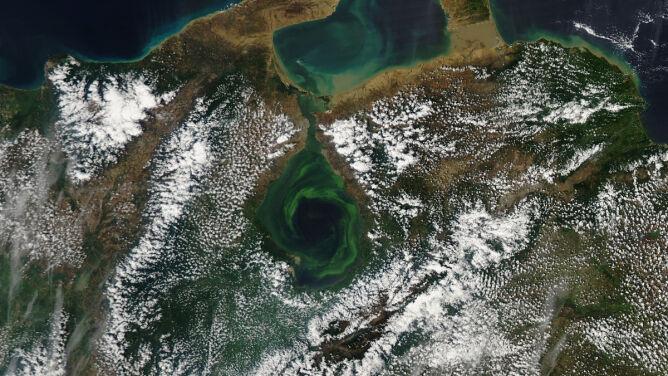 Zielony wir w jeziorze, <br />nad którym rozstępują się chmury